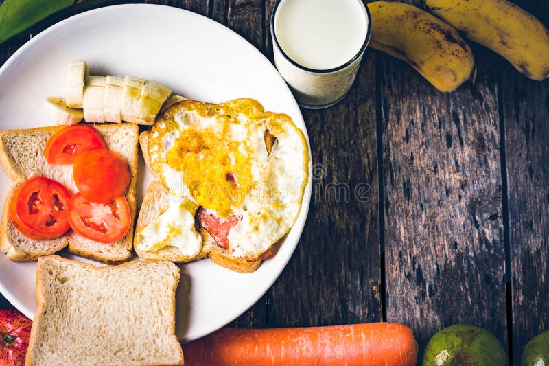 Western breakfast : toast egg and fruit on wooden table stock images