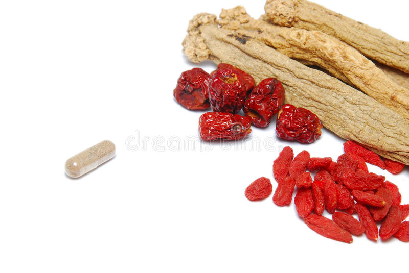 Western and Chinese traditional medicine. An assortment of Chinese traditional herbs and a single Western medicinal capsule. Suitable for concepts such as royalty free stock images