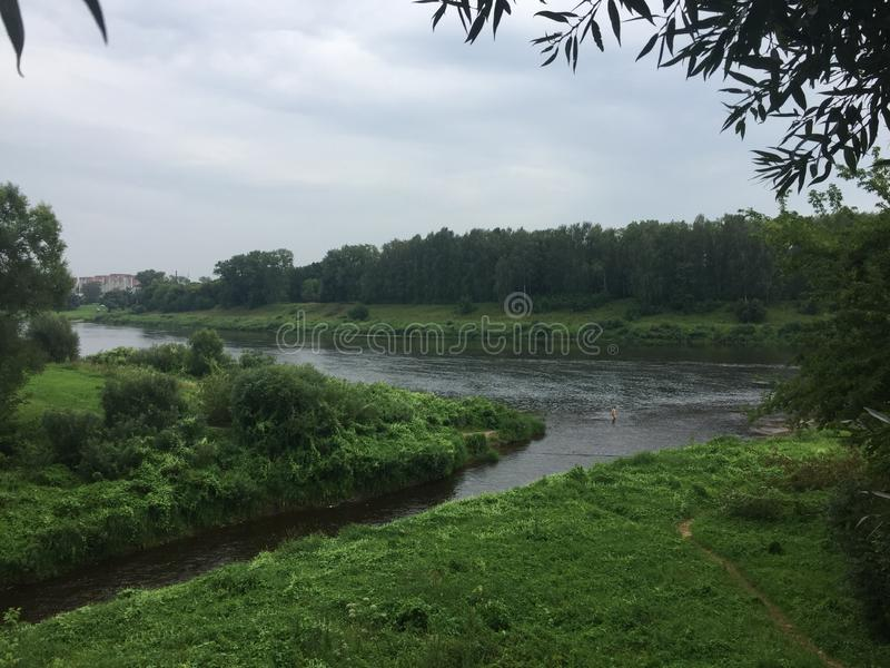 Western Dvina river in Belarus. The Western Dvina river in Belarus in summer against green trees stock photography