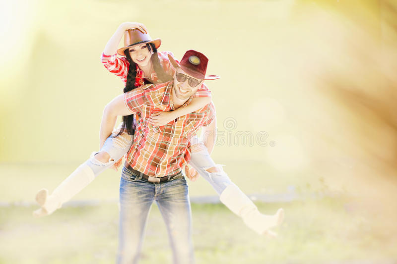 Western happy couple laughing and fooling around. Cowboy and Cowgirl Couple royalty free stock images