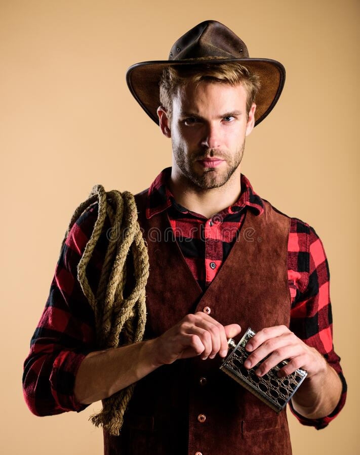 Western life. Sheriff concept. Bourbon whiskey. Western culture. Man wearing hat hold rope and flask. Lasso tool stock images