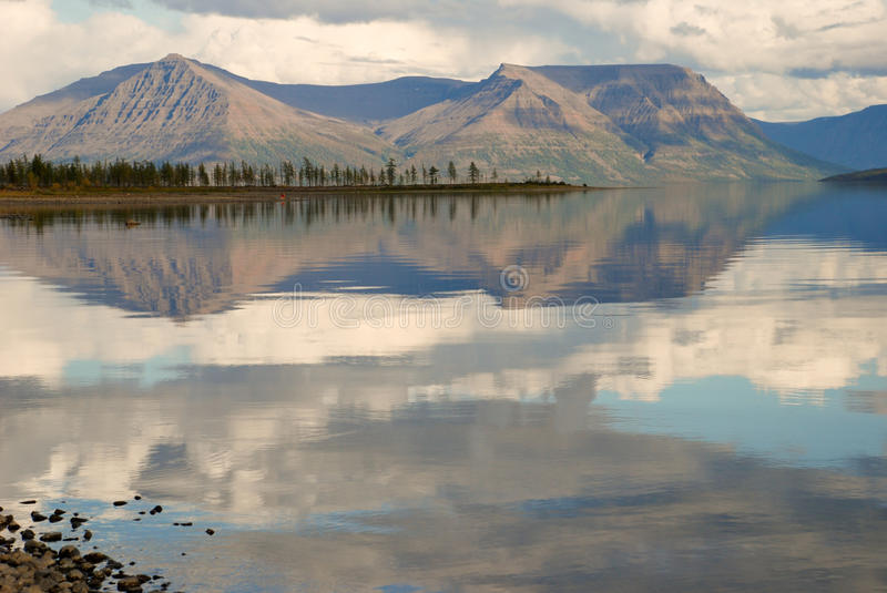 Lake Lama and reflected in the water clouds and mountains of the royalty free stock photos