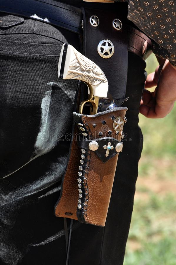 Western pistol gun with ivory handle grip in leather holster gun belt worn by old west cowboy. Western pistol gun with carved ivory handle grip in leather royalty free stock photos