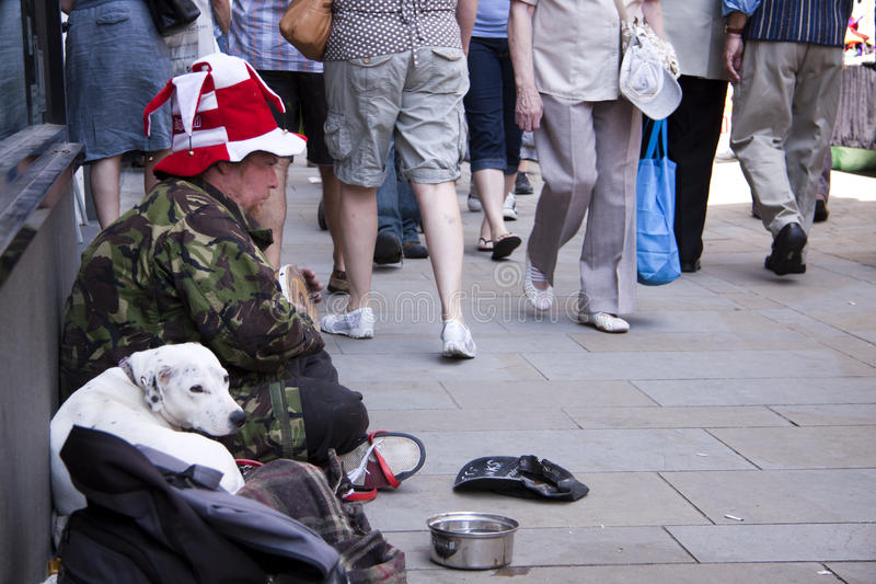 Western poverty. A homeless man and his dog begging on the streets of Brittan as people walk past him stock photography