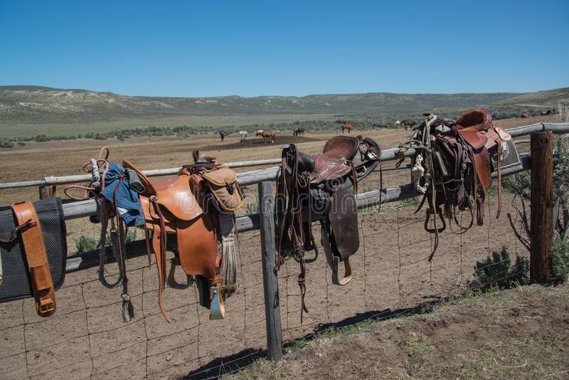 Western riding tack saddles, bridles and horse blankets on wooden corral post after a trail ride stock images