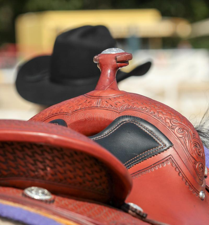 Western saddle with cowboy hat and leather harness royalty free stock images