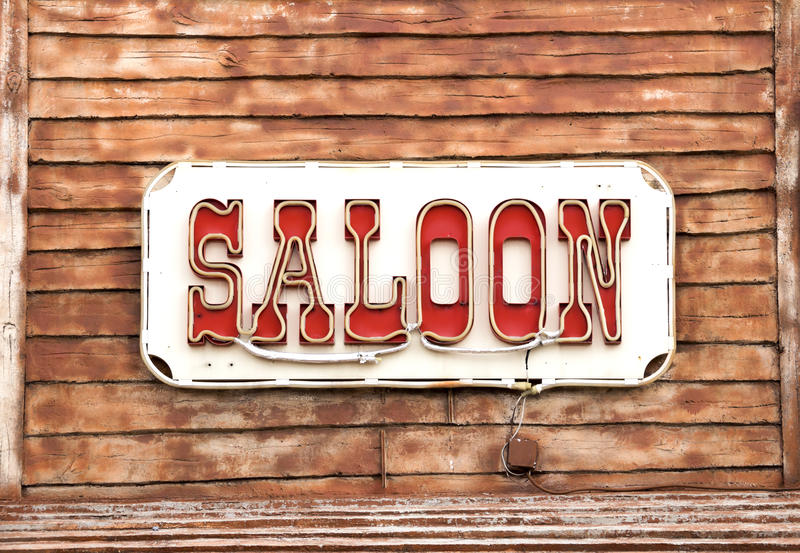 Western Saloon. Sign on wooden background royalty free stock photos