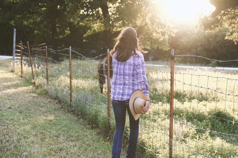 Western scene during sunset shows woman with cowboy hat standing at fence. royalty free stock photo