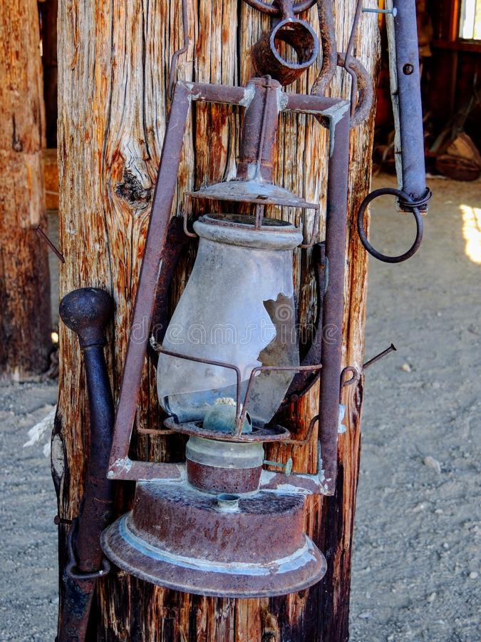Western style rusty antique broken oil lantern hanging at farm countryside old lamp vintage style hang on wood background. stock photography