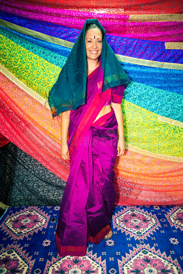 Western woman with Indian clothes. Sari. A beautiful Caucasian smiling woman dressing typical Indian clothing. Dress symbol of India: Sari. Many bright colors royalty free stock photos