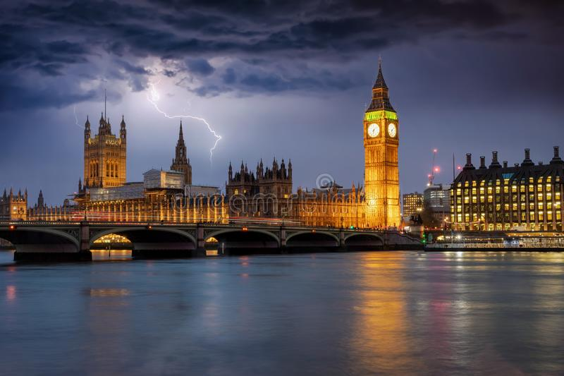 The Westminster Palace and Big Ben clocktower in London during a thunderstorm. The Westminster Palace and Big Ben clocktower in London by night during a royalty free stock photo