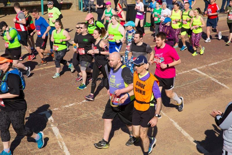 Weston Super halv maraton på Weston-toppen-stoen, Somerset på den söndag 24th mars 2019 med löparna på Birnbeck Rd royaltyfri fotografi