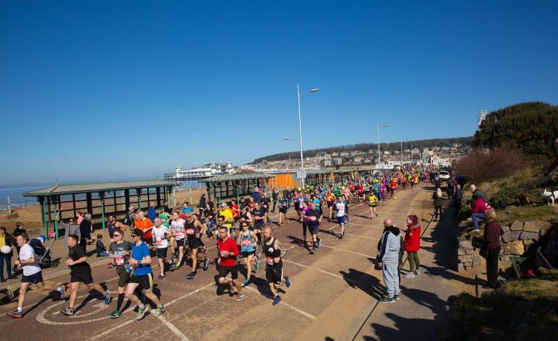 Weston Super Mare halv maraton på Weston-toppen-stoen, Somerset på den söndag 24th mars 2019 med löparna på Birnbeck Rd royaltyfri fotografi