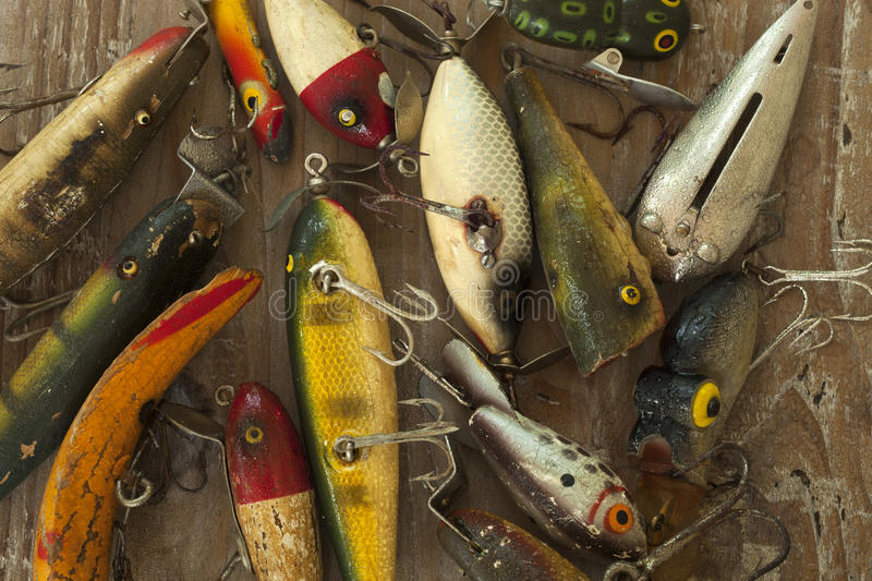 Wet antique fishing lures viewed from above on a rough wood surf. Ace stock images