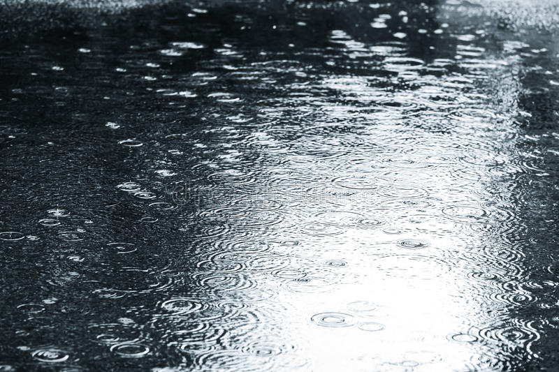 Wet asphalt with drops on water puddle during rainy weather stock photography