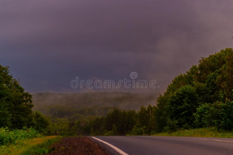 Wet asphalt after rain. Thick rain clouds. The road along the forest. Ural Mountains in rainy summer weather.  royalty free stock images
