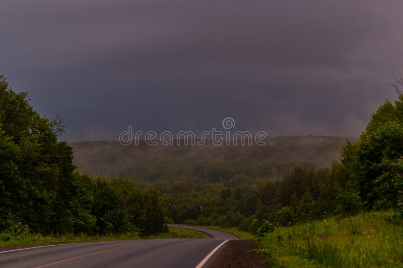 Wet asphalt after rain. Thick rain clouds. The road along the forest. Ural Mountains in rainy summer weather.  royalty free stock image