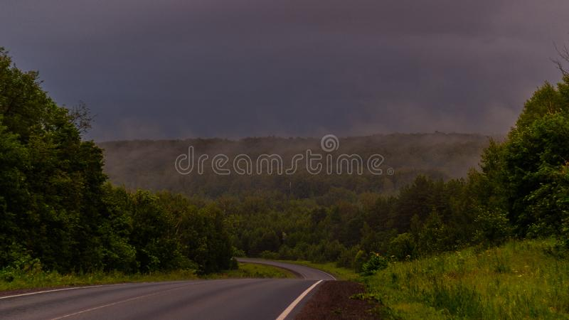 Wet asphalt after rain. Thick rain clouds. The road along the forest. Ural Mountains in rainy summer weather.  royalty free stock photography