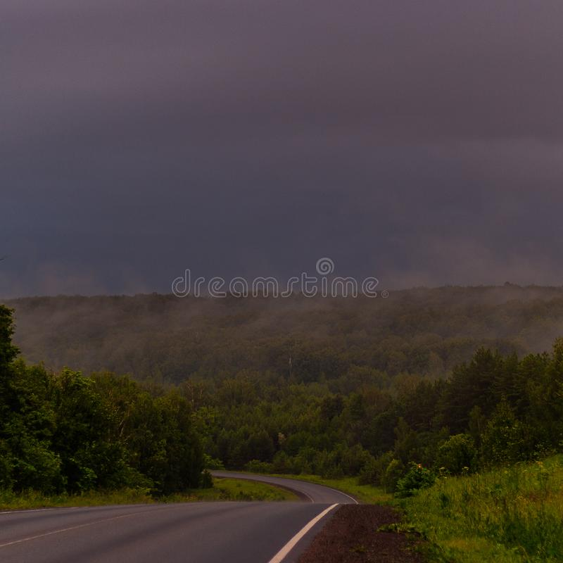 Wet asphalt after rain. Thick rain clouds. The road along the forest. Ural Mountains in rainy summer weather.  stock photography