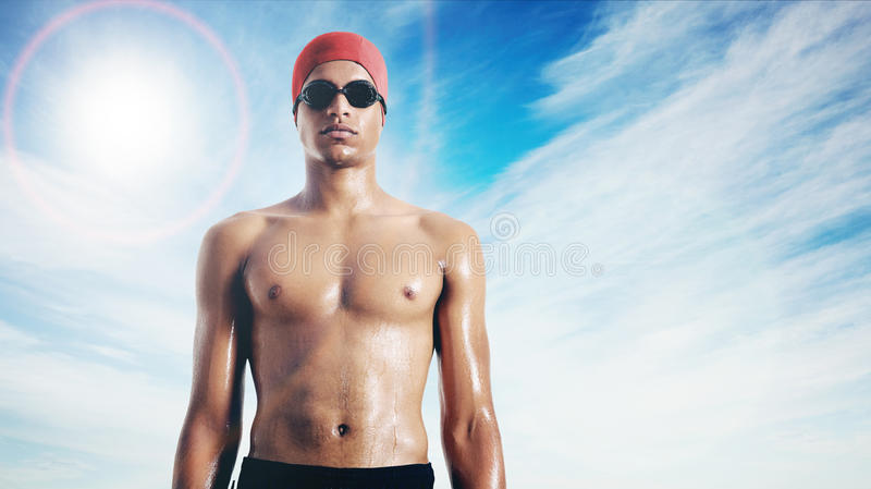 Wet attractive African American swimmer against sky with lens glare. Head and torso of a serious-looking fit wet latin swimmer in red cap and black goggles stock image