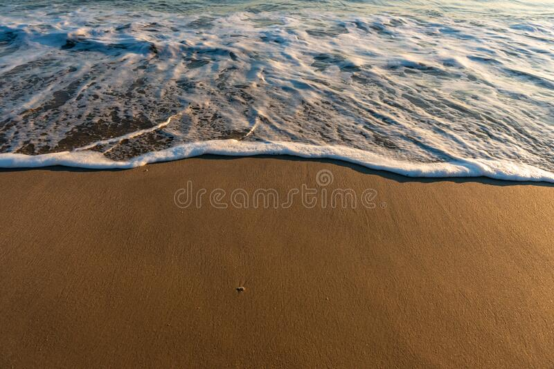 Wet beach sand and ocean. Tide royalty free stock photography