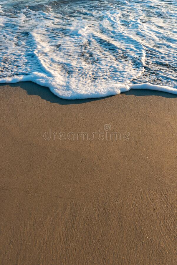 Wet beach sand and ocean. Tide royalty free stock photos
