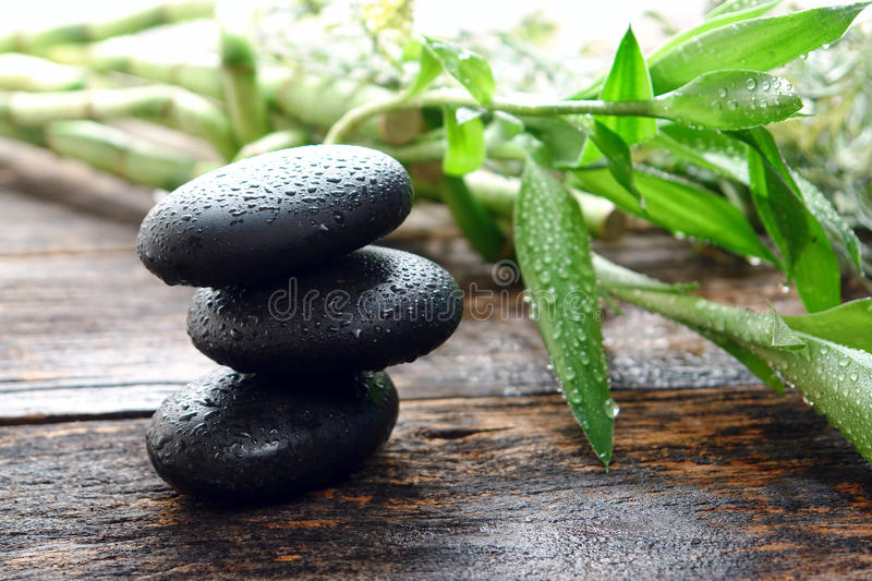 Wet Black Polished Massage Stones Balanced in Spa stock photo