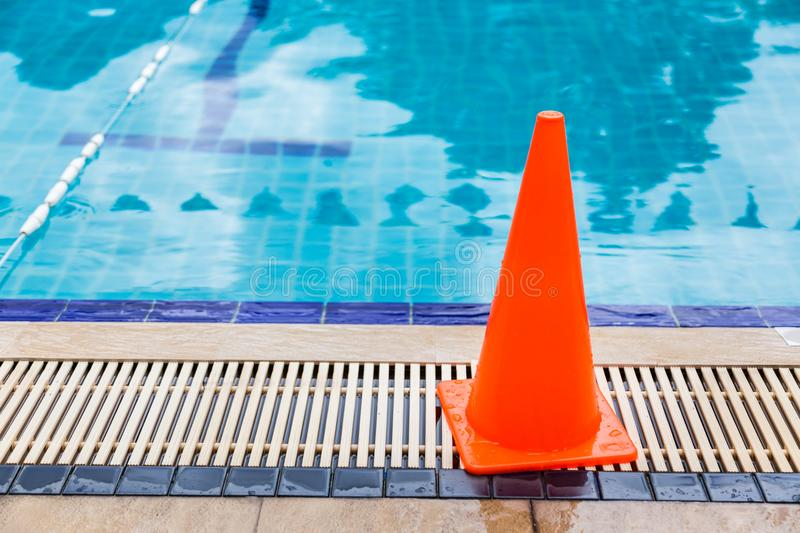 Wet bright orange cone placed by the swimming pool side as safety precaution sign. Good for safety concept stock image