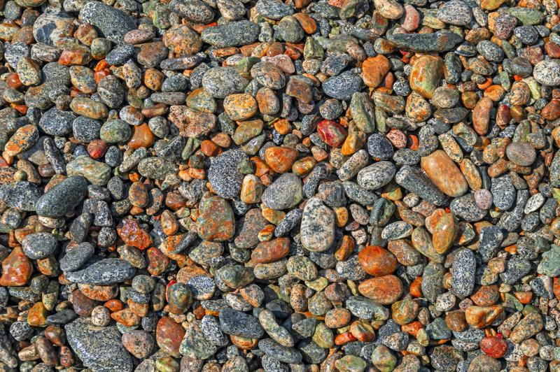 Wet bright stones with smooth texture. Abstract art pattern background. Ocean coast, backdrop wallpaper. Sea pebbles decoration. Abstract shape royalty free stock photography