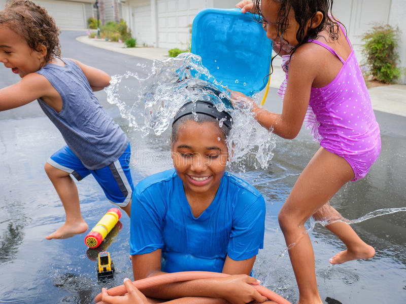 Wet Brother and Sisters Playing Outside with Water stock image