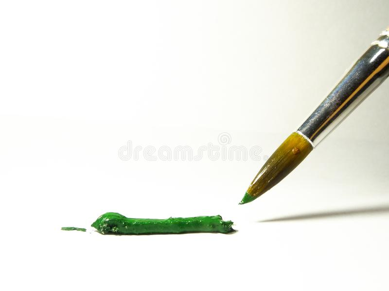 Wet brush over green paint close-up. stock photo