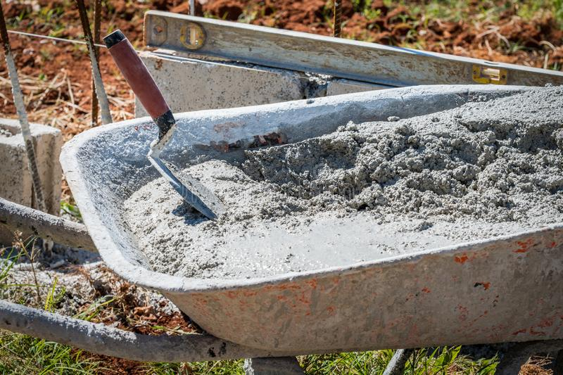 Wet cement and trowel in wheelbarrow royalty free stock image