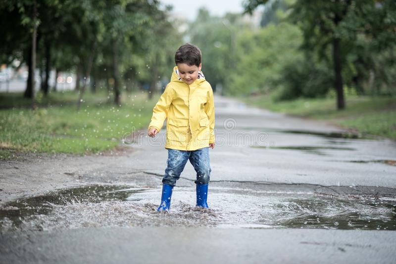 A wet child is jumping in a puddle. Fun on the street. Tempering in summer stock image