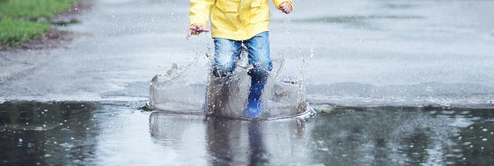 A wet child is jumping in a puddle. Fun on the street. Tempering in summer stock photo