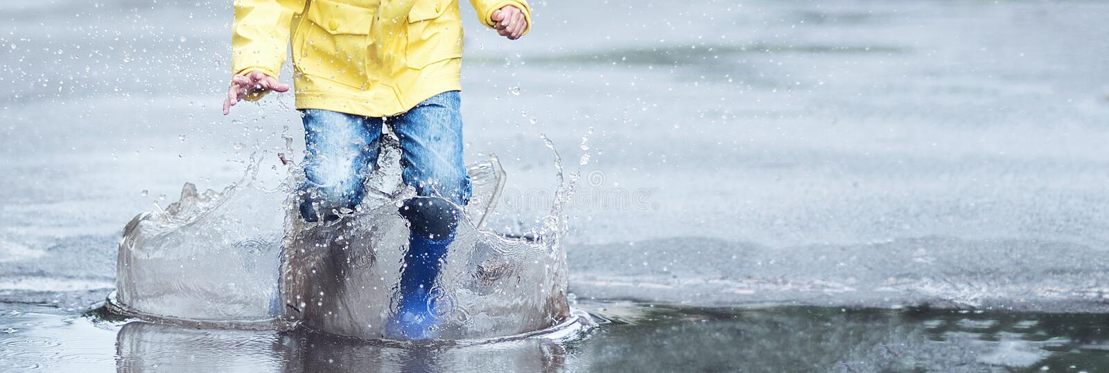 A wet child is jumping in a puddle. Fun on the street. Tempering in summer stock photos