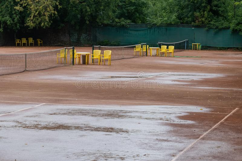Wet clay tennis court after the rain, match cancelled. Background, texture, game, health, net, outdoor, pattern, recreation, red, sport, summer, active stock photo