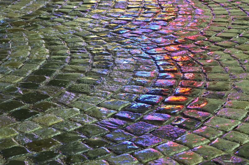 Wet cobblestone with blue and red lights reflected by rain water. royalty free stock photo