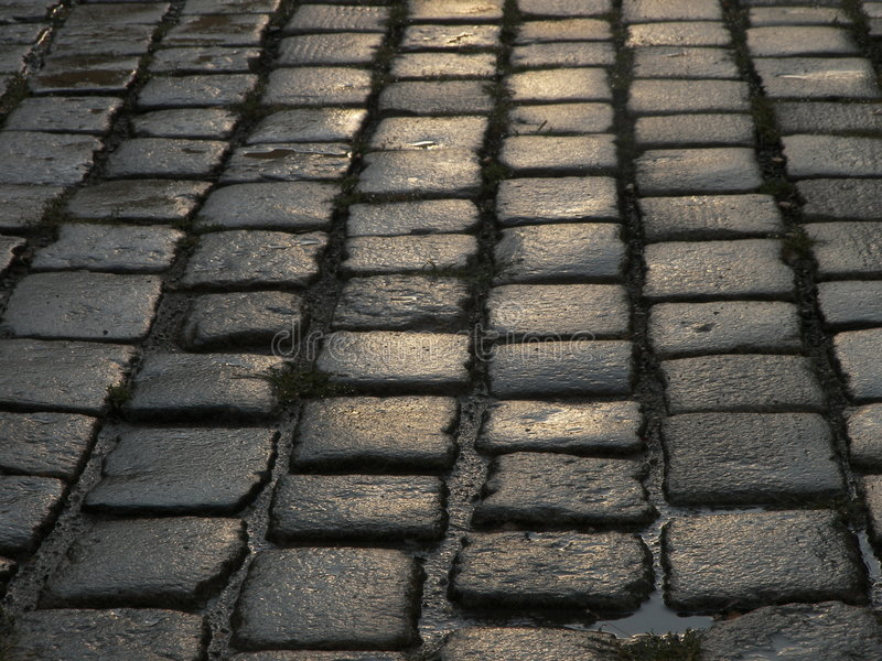 Wet cobblestone street closeup stock photos