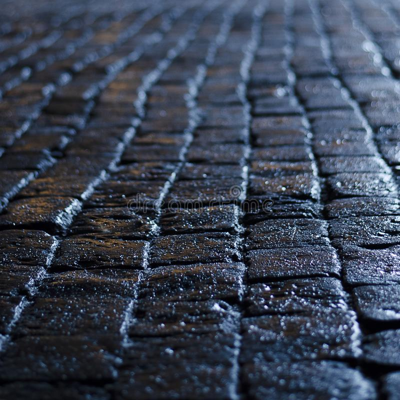 Wet cobblestones with blue reflected light at night. Wet cobblestones with blue reflected light from the lanterns at night royalty free stock photo