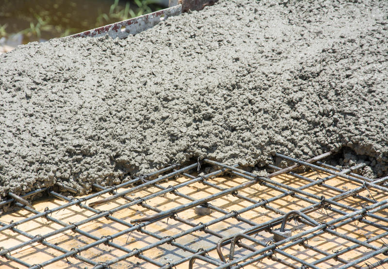The wet concrete is poured on wire mesh steel reinforcement stock image