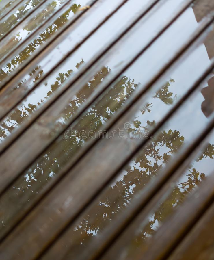 Wet cottage deck. Reflections in puddles on wooden planks after summer rain stock photos