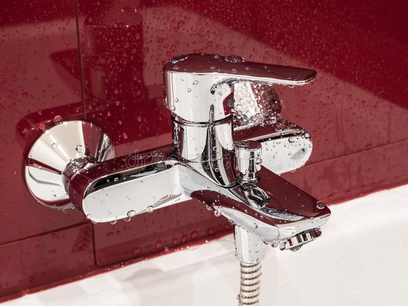 Wet faucet covered by water drops in a modern bathroom. Wet faucet covered by water drops in a modern reconstructed bathroom with red tile walls stock photography