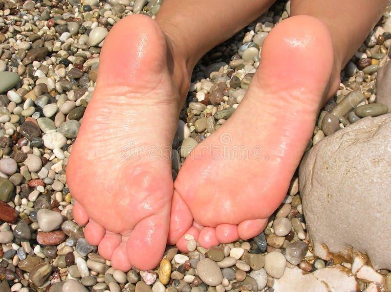 Wet feet. Close-up over rocks stock photos