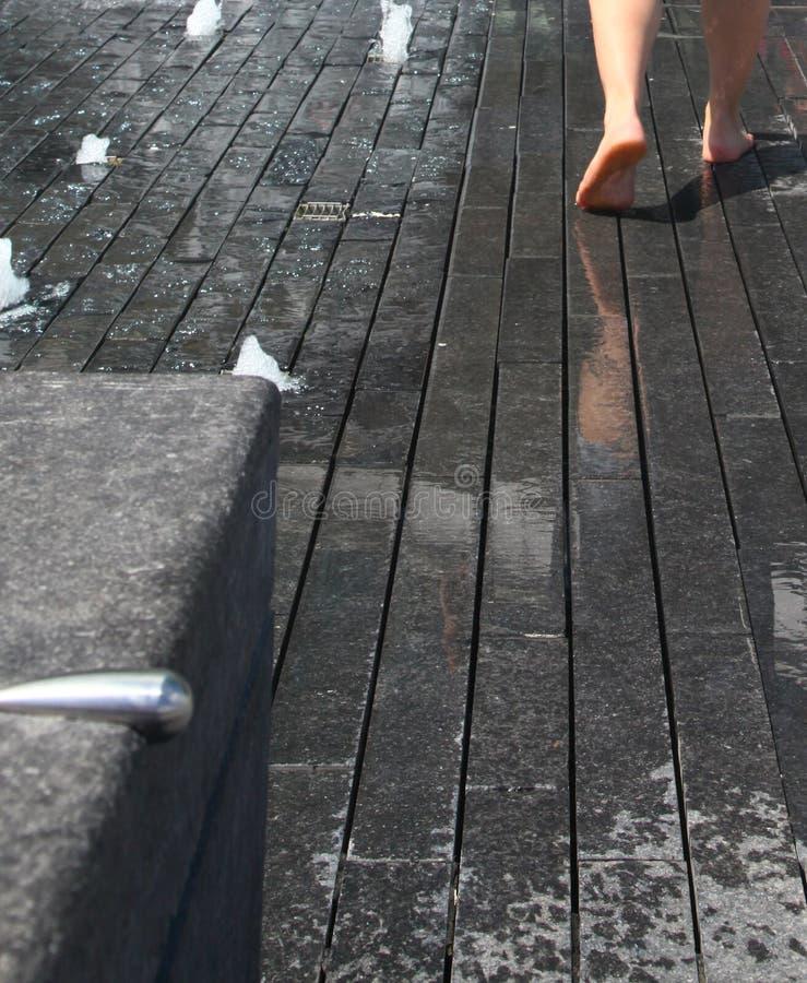 Wet feet. A pair of wet feet walking on wet tiles royalty free stock image