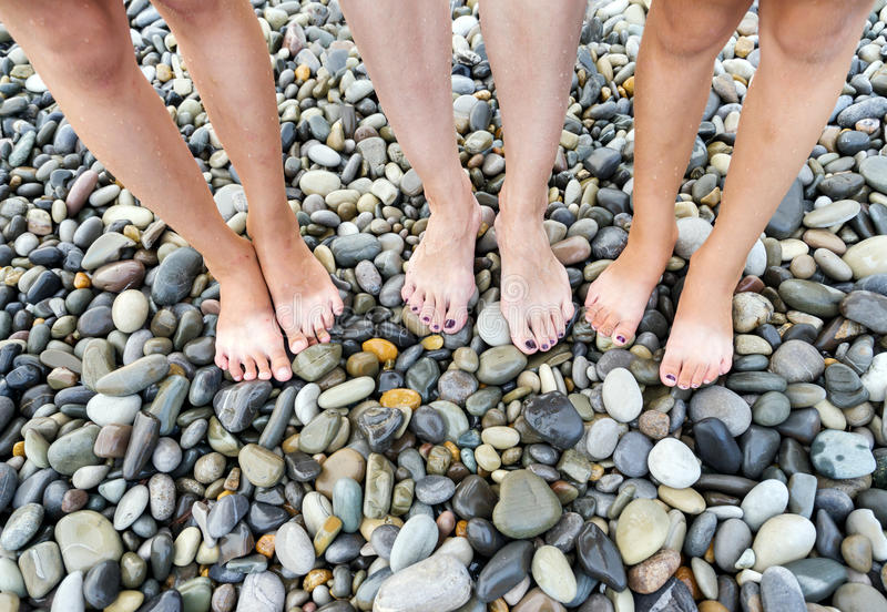 Wet feet of mother and child. Wet feet of mother and small children's on beach the sea in a summer sunny day. Family holiday royalty free stock image