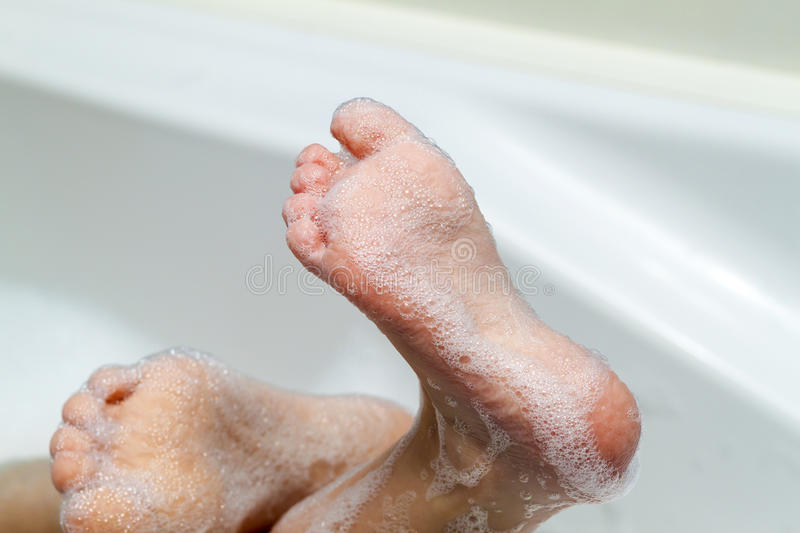 Wet feet with wrinkled skin and soap bubbles in bath. Hygiene an. D cosmetics concept royalty free stock photo