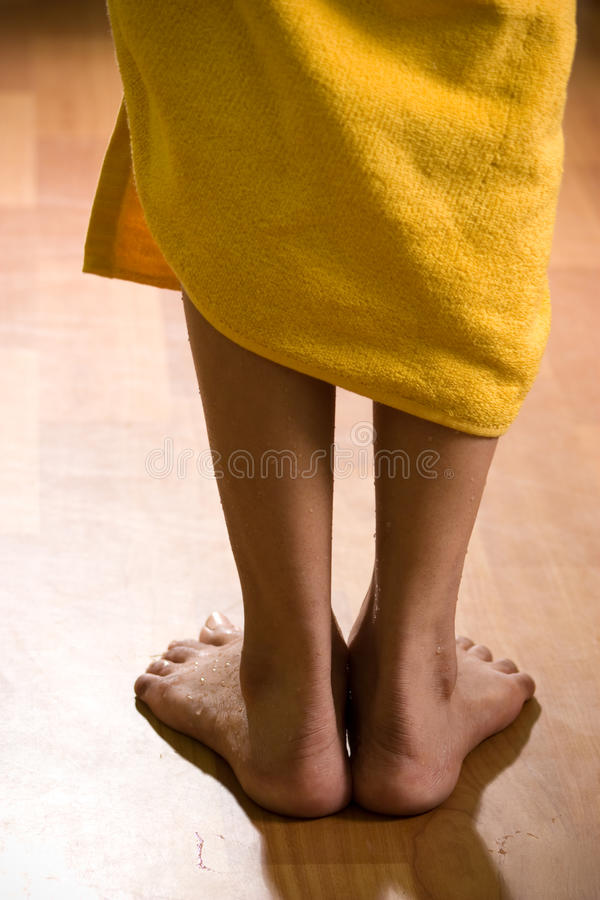 Wet female legs with towel on wooden floor royalty free stock photo