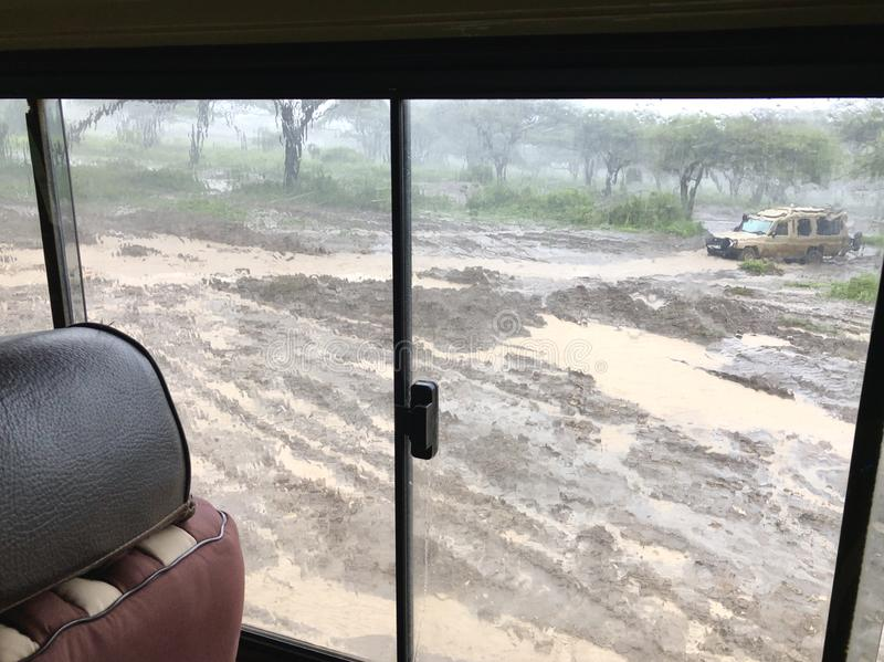 Wet flooded road. Soil erosion after storm, view thru four-wheel drive at Serengeti National Park in Tanzania, Africa. Wet flooded road. Soil erosion after storm stock photo