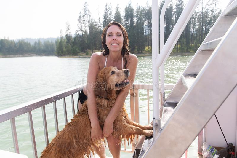 Pretty woman with wet golden retriever dog outside at a lake royalty free stock photos