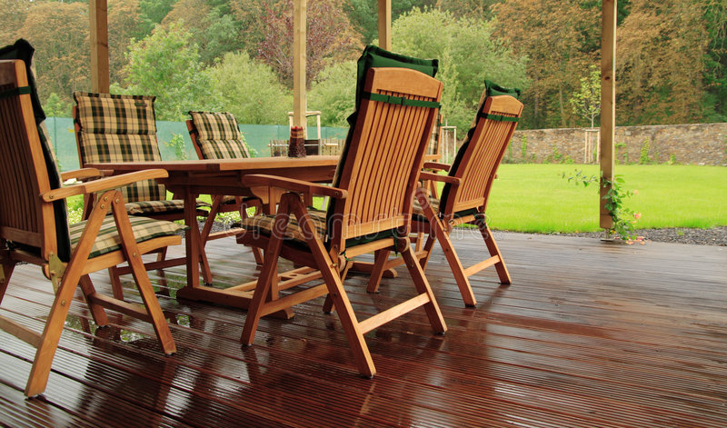 Wet garden. Garden furniture on a wet wooden floor